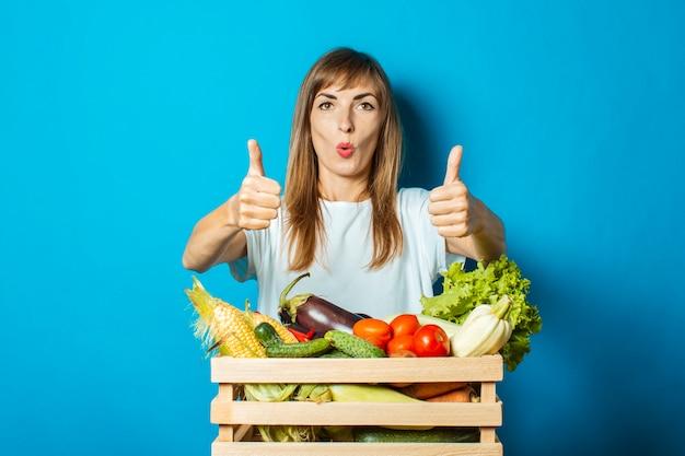 Jonge vrouw met een verbaasd gezicht houdt een doos met verse groenten op blauw. goed oogstconcept, natuurlijk product