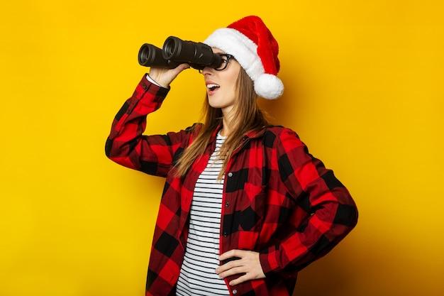 Jonge vrouw met een verbaasd gezicht in een kerstmuts en een rood shirt in een kooi kijkt door een verrekijker