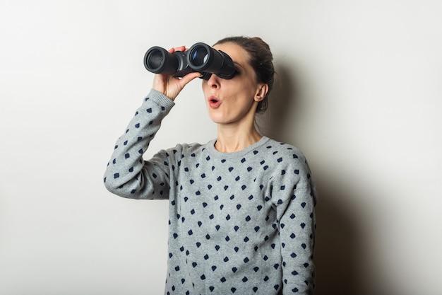 Jonge vrouw met een verbaasd gezicht in een trui kijkt door een verrekijker op een lichte achtergrond.