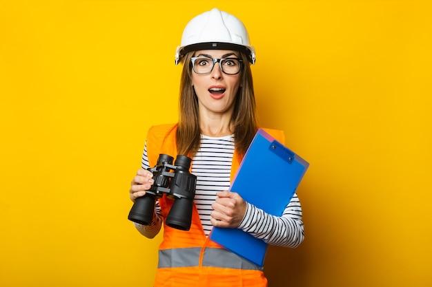 Jonge vrouw met een verbaasd gezicht in een vest en bouwvakker houdt een klembord en een verrekijker op geel