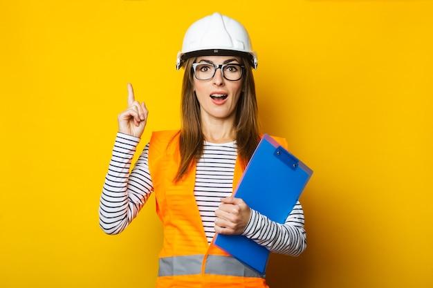 Jonge vrouw met een verbaasd gezicht in een vest en bouwvakker houdt een klembord op geel
