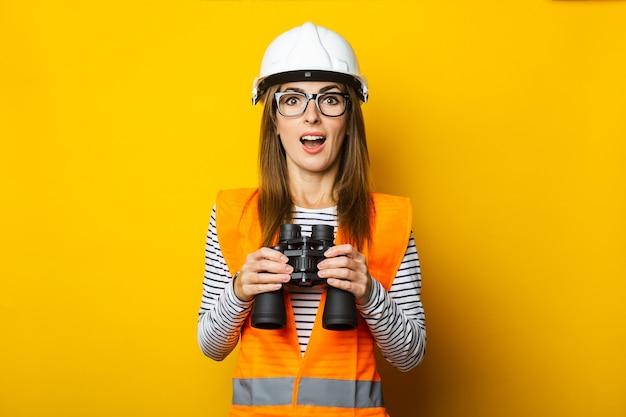 Jonge vrouw met een verbaasd gezicht in een vest en bouwvakker houdt een verrekijker op geel
