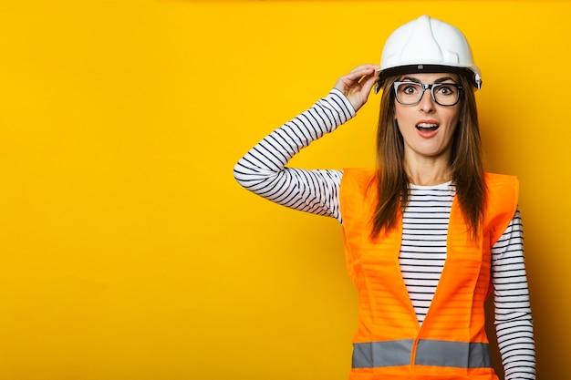Jonge vrouw met een verbaasd gezicht in een vest en bouwvakker op geel
