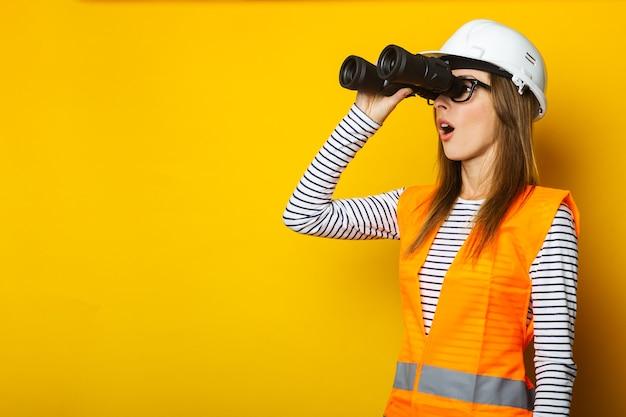 Jonge vrouw met een verbaasd gezicht in een vest en een helm kijkt door een verrekijker op geel