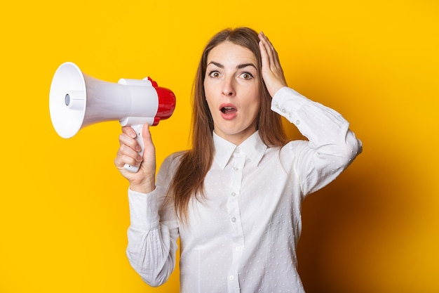 Jonge vrouw met een verbaasd gezicht in een wit overhemd houdt een megafoon in haar handen op een gele achtergrond. inhuurconcept, hulp gezocht. banier.