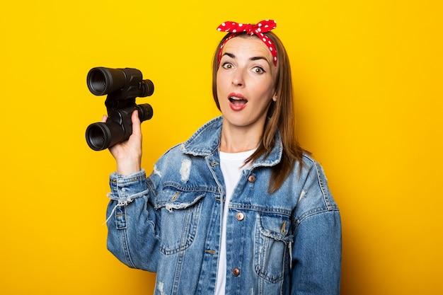 Jonge vrouw met een verbaasd gezicht in spijkerbroek en een vlot op haar hoofd houdt een verrekijker in haar handen op een gele muur. banner.