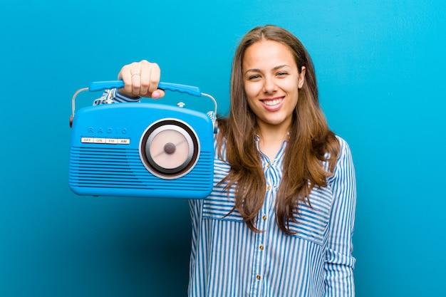 Jonge vrouw met een vintage radio op blauw