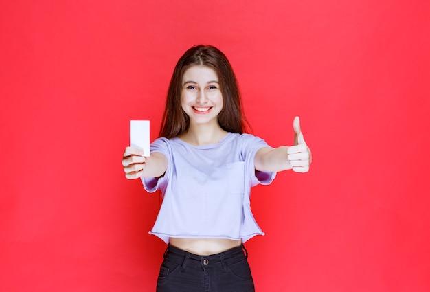 Jonge vrouw met een visitekaartje en duim opdagen.