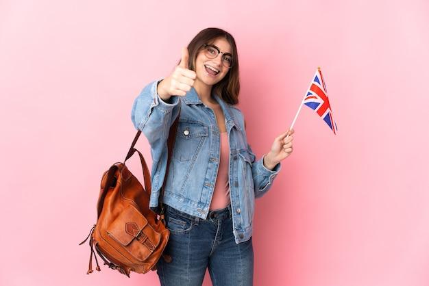 Jonge vrouw met een vlag van het verenigd koninkrijk geïsoleerd op roze met duimen omhoog omdat er iets goeds is gebeurd