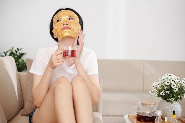 Jonge vrouw met een vochtinbrengend bladmasker op haar gezicht die een kopje kruidenthee drinkt en dromerig over een mooie vlekkeloze huid