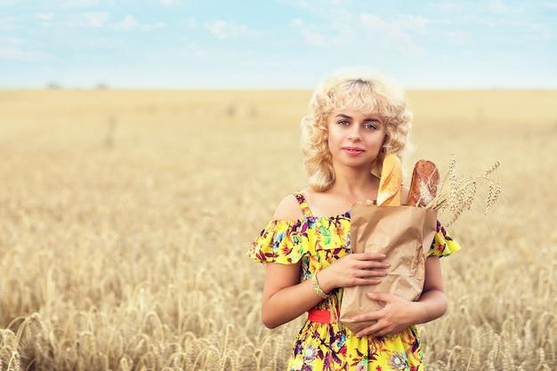 Jonge vrouw met een volledig pak brood in een veld met rijpe tarwe