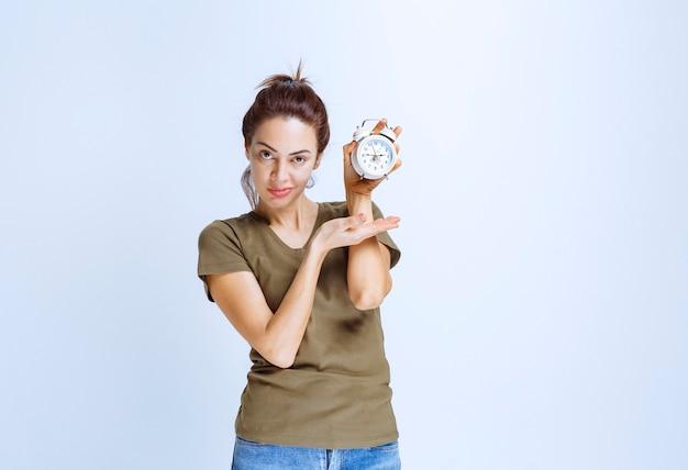 Jonge vrouw met een wekker en ziet er tevreden uit omdat ze nooit te laat is