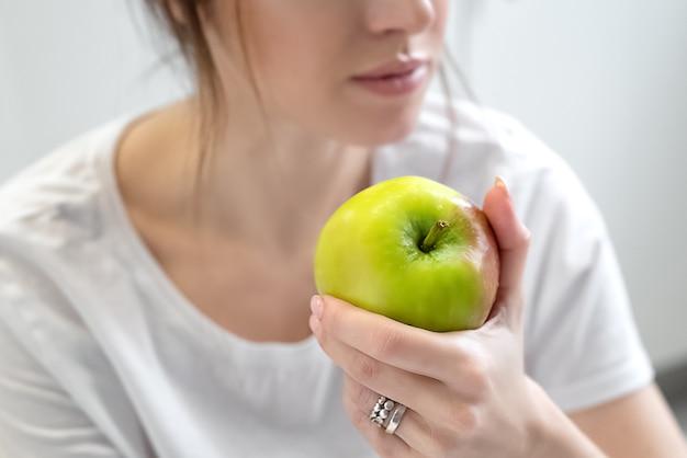 Jonge vrouw met een wit t-shirt houdt groene rijpe appel in haar hand. dieet en gezond eten