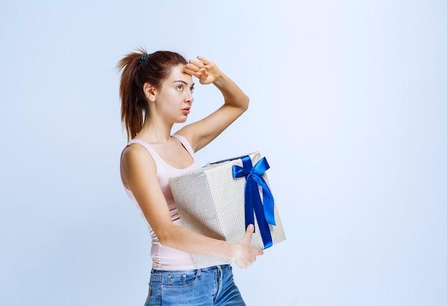 Jonge vrouw met een witte geschenkdoos omwikkeld met blauw lint en hand op haar voorhoofd om naar voren te kijken