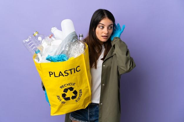 Jonge vrouw met een zak vol plastic flessen om te recyclen geïsoleerd op paarse muur luisteren naar iets door hand op het oor te leggen