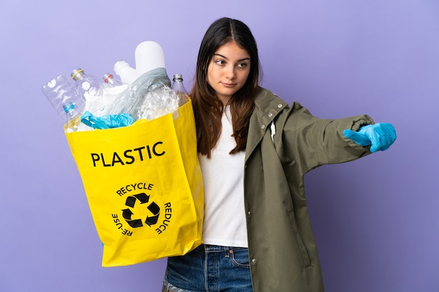 Jonge vrouw met een zak vol plastic flessen om te recyclen geïsoleerd op paarse muur met een duim omhoog gebaar
