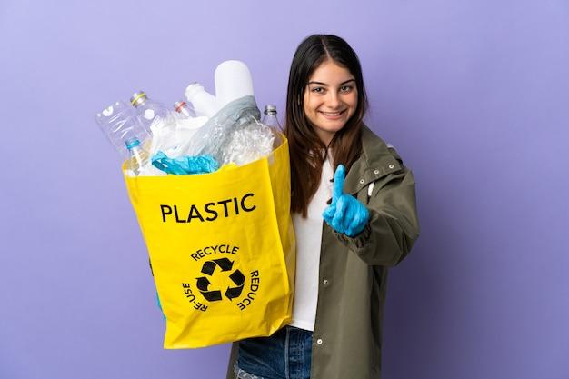 Jonge vrouw met een zak vol plastic flessen om te recyclen geïsoleerd op paarse muur tonen en opheffen van een vinger