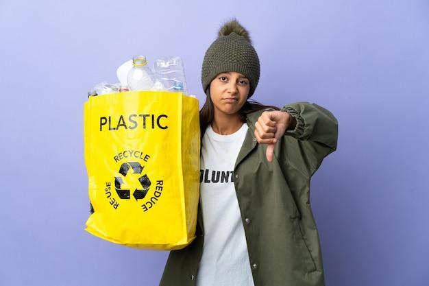 Jonge vrouw met een zak vol plastic met duim omlaag met negatieve uitdrukking