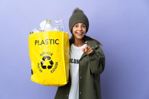 Jonge vrouw met een zak vol plastic verrast en wijst naar voren