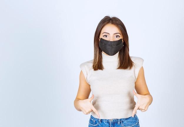 Jonge vrouw met een zwart medisch masker dat met wijsvingers naar beneden wijst.