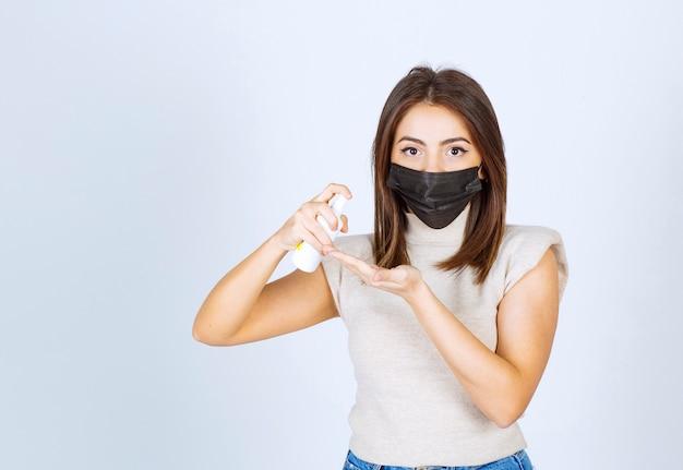 Jonge vrouw met een zwart medisch masker die een spray gebruikt