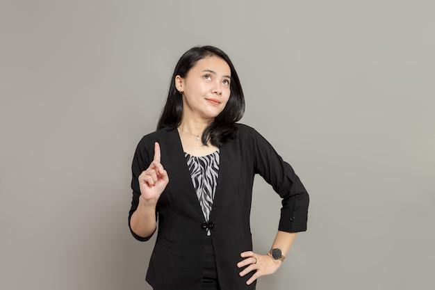 Jonge vrouw met een zwart pak die met één hand omhoog kijkt en omhoog wijst