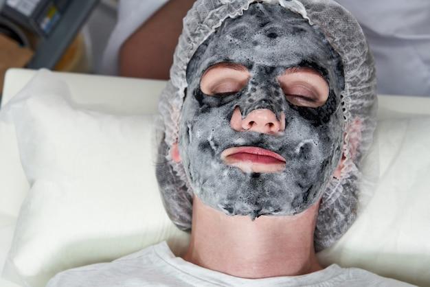 Jonge vrouw met een zwart zuurstofbellenmasker op haar gezicht in schoonheidssalon