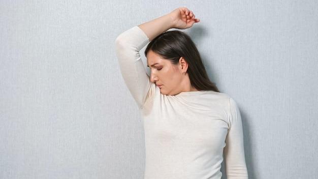 Jonge vrouw met een zweetprobleem onder de oksels. het concept stinkt. hyperhidrose.