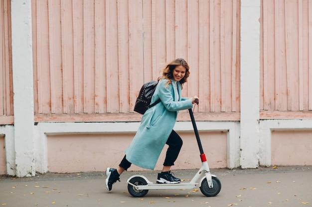 Jonge vrouw met elektrische scooter in blauwe jas in de stad