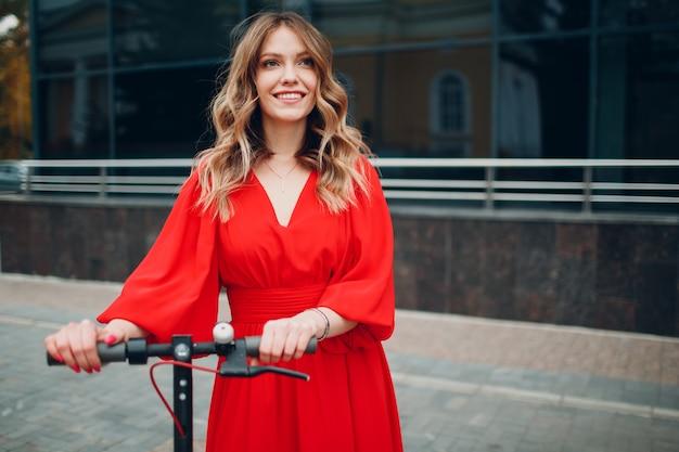 Jonge vrouw met elektrische scooter in rode jurk in de stad