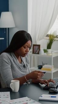Jonge vrouw met elektronische creditcard die online betaling typt op het toetsenbord van de computer terwijl ze een elektronische tablet bestelt tijdens online verkoop