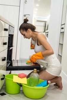 Jonge vrouw met emmer wasmiddelen die haar nieuwe keuken schoonmaakt