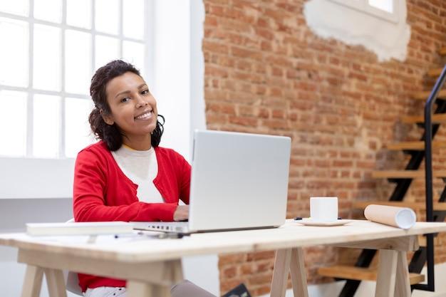 Jonge vrouw met exotische kenmerken die lacht tijdens het gebruik van haar laptop aan de balie. ruimte voor tekst. werk vanuit huis concept.