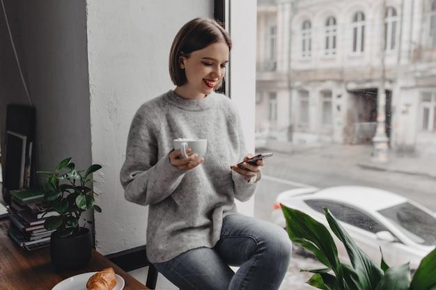 Jonge vrouw met felle lippenstift is chatten op telefoon met glimlach, kopje cacao met marshmallows, poseren bij raam met croissant op houten tafel.