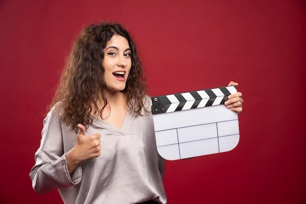 Jonge vrouw met filmklapper die duimen opgeeft.