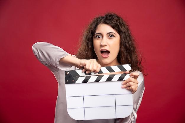 Jonge vrouw met filmklapper schreeuwen.
