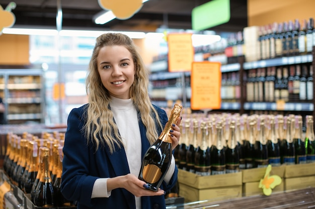 Jonge vrouw met fles alcohol drinken in slijterij. eigenaar van een klein bedrijf