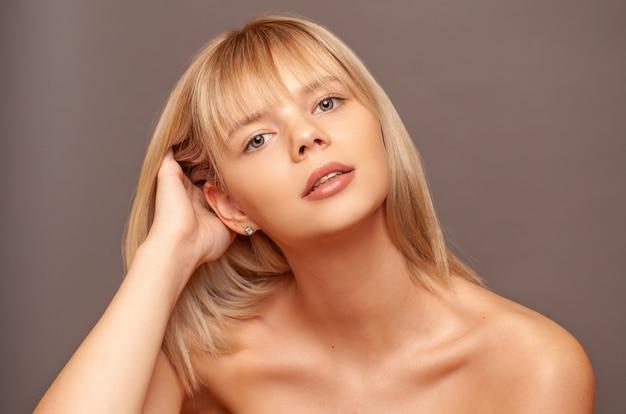 Jonge vrouw met frisse gezonde huid en haren aan haar gezicht te raken.