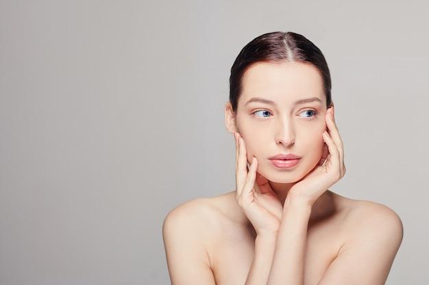 Jonge vrouw met frisse schone huid die haar gezicht met beide handen raakt
