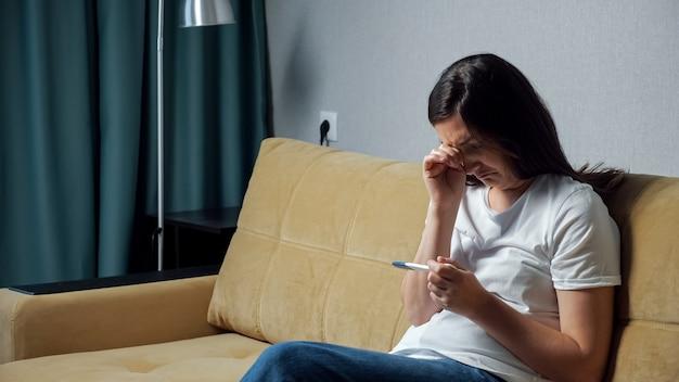Jonge vrouw met frustratie kijkt naar zwangerschapstest.