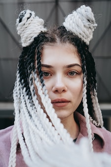 Jonge vrouw met futuristische looks meisje met zwarte en witte dreadlocks of pigtails tegen de achtergrond van een futuristisch gebouw