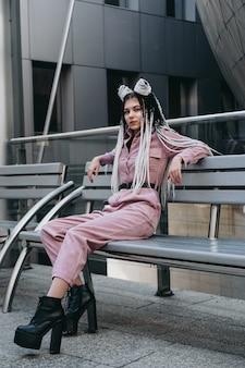 Jonge vrouw met futuristische looks, zittend op een bankje meisje met zwarte en witte pigtails tegen de achtergrond van een futuristisch gebouw