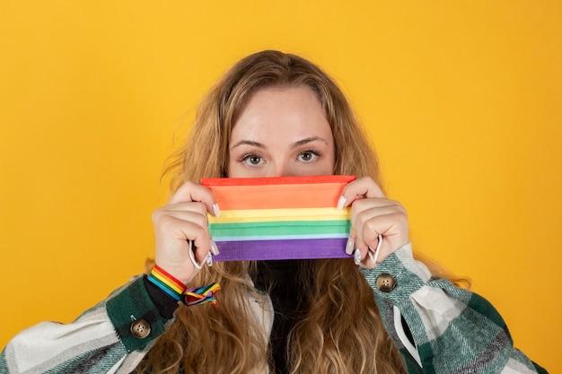 Jonge vrouw met gay pride-vlag die het symbool van de regenboogvlag van lgbt houdt