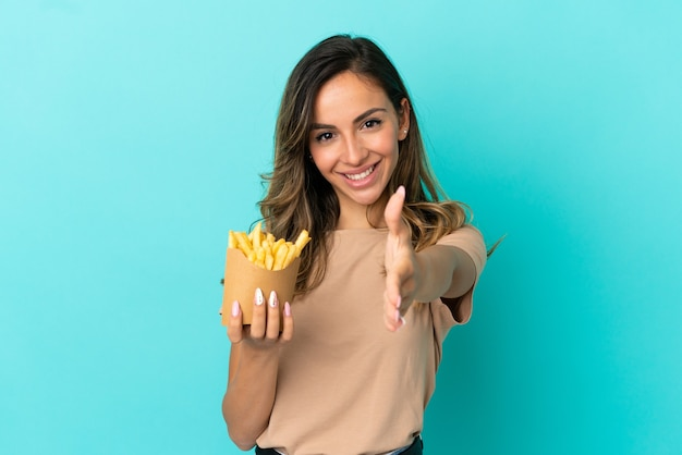 Jonge vrouw met gebakken chips over geïsoleerde achtergrond handen schudden voor het sluiten van een goede deal