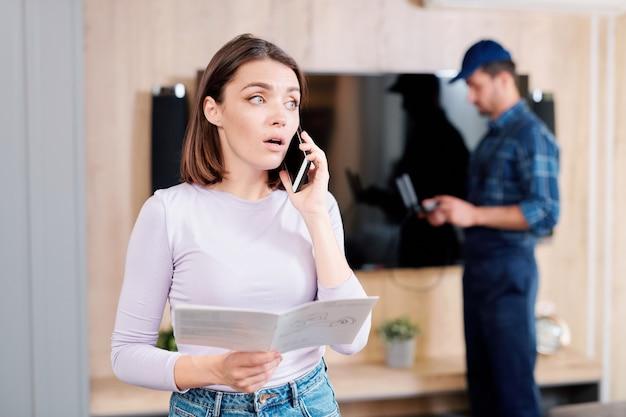 Jonge vrouw met gebruiksinstructies gids huishoudelijke reparatieservice aan de telefoon raadplegen