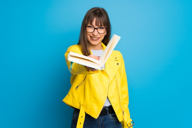 Jonge vrouw met geel jasje dat een boek houdt en het aan iemand geeft