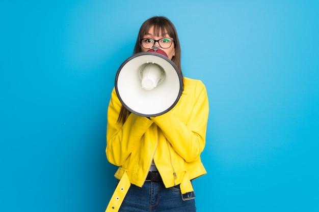 Jonge vrouw met geel jasje op blauwe achtergrond die door een megafoon schreeuwt