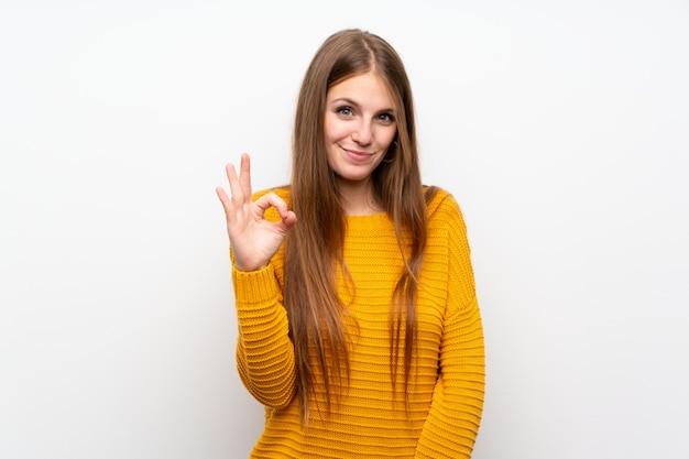 Jonge vrouw met geel over geïsoleerde witte muur die een ok teken met vingers toont
