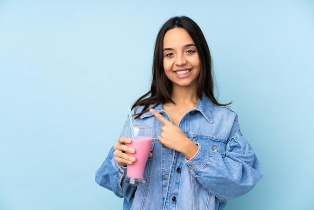 Jonge vrouw met geïsoleerde aardbeimilkshake