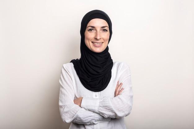 Jonge vrouw met gekruiste armen gekleed in een wit overhemd en hijab lachend
